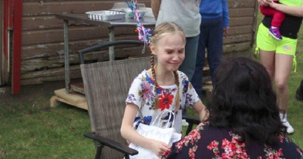 Dívka otvírá svůj narozeninový dárek od macechy, který ji přivedl k pláči