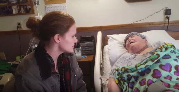 Zdravotní sestra se vkrádá na pokoj pacientky a o chvíli později kamera zaregistruje její nádherné gesto